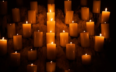 Rows of burning candles surrounded by melted candle wax