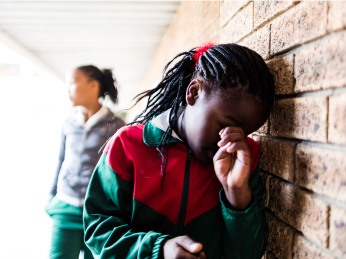 A school girl stands leaning against a wall crying, she is being bullied by other school girls.